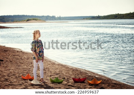 Dreamy girl posing with paper boats at lake - stock photo