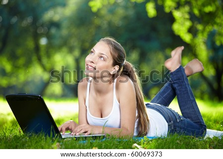 Dreamy girl with a laptop in the park - stock photo