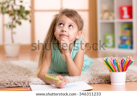 dreamy kid girl draws with color pencils lying on floor at home - stock photo