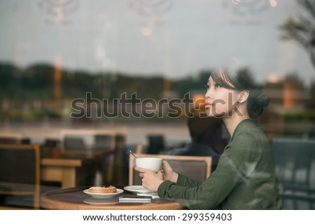 Dreamy lovely young woman having lunch in a cafe - stock photo