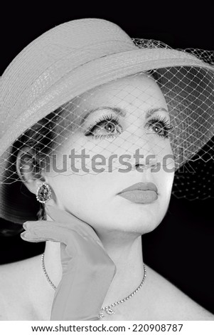 Dreamy retro/vintage portrait of woman wearing retro hat with netting coming down her face.  Black and White - stock photo