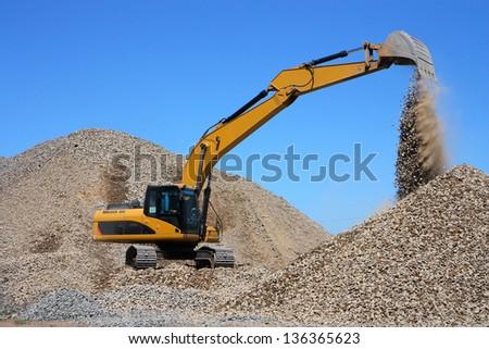 Dredge loads a rubble against the blue sky - stock photo