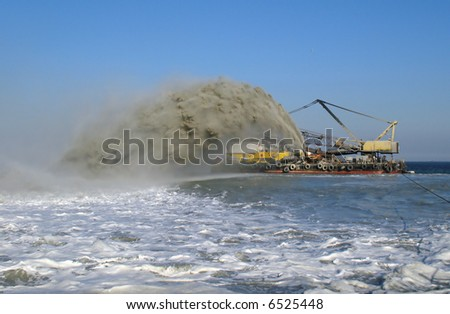 Dredger pumps sand onto beach - stock photo