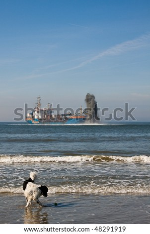 Dredger with a dog on the beach - stock photo
