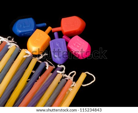 Dreidels and Chanukah wax candles of different colors shown together isolated against a black background. - stock photo