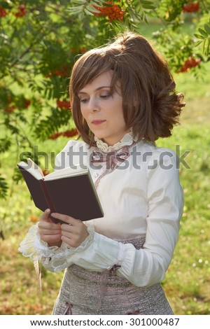 Dressed in retro clothes beautiful girl reads book with slight smile on her face                                - stock photo