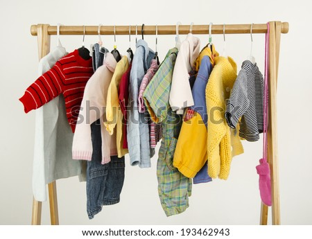 Dressing closet with complementary clothes arranged on hangers.Colorful wardrobe of newborn,kids, babies full of all clothes, shoes,accessories and toys - stock photo