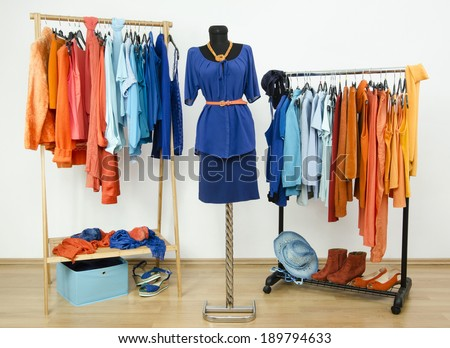 Dressing closet with complementary colors blue and orange clothes arranged on hangers and an outfit on a mannequin. Wardrobe full of all shades of blue an orange clothes, shoes and accessories. - stock photo
