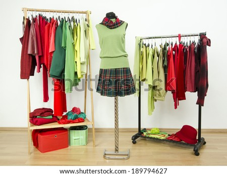 Dressing closet with complementary colors red and green clothes arranged on hangers and an outfit on a mannequin. Wardrobe full of all shades of green and red clothes and accessories. - stock photo