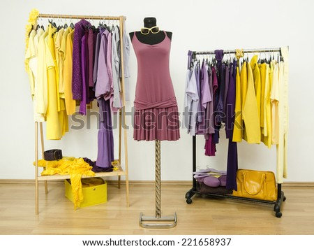Dressing closet with complementary colors violet and yellow clothes.Wardrobe with purple and yellow clothes arranged on hangers and a summer dress on a mannequin. - stock photo