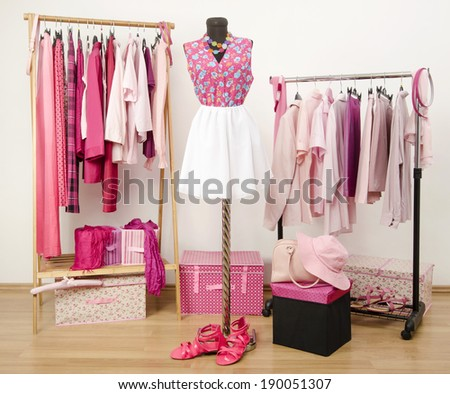 Dressing closet with pink clothes arranged on hangers and an outfit on a mannequin.  Wardrobe full of all shades of pink clothes, shoes and accessories. - stock photo