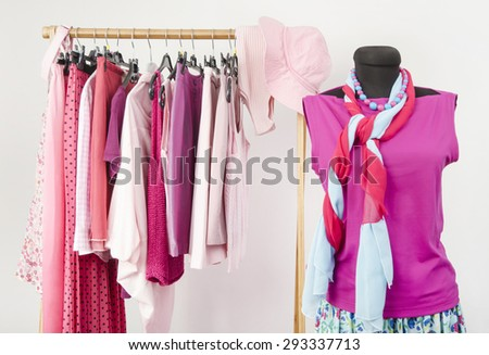 Dressing closet with pink clothes arranged on hangers and an outfit on a mannequin. Wardrobe full of all shades of pink clothes and accessories. - stock photo