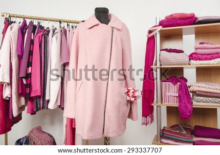 Dressing closet with pink clothes arranged on hangers and shelf, a coat on a mannequin. Fall winter wardrobe full of all shades of pink clothes, shoes and accessories. - stock photo