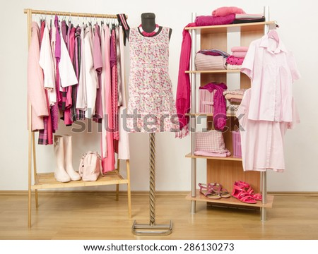 Dressing closet with pink clothes arranged on hangers and shelf, close up on outfit on a mannequin. Wardrobe full of all shades of pink clothes and accessories. - stock photo