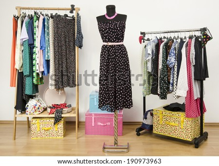 Dressing closet with polka dots clothes arranged on hangers and a dress on a mannequin. Colorful wardrobe with polka dots clothes and accessories.  - stock photo