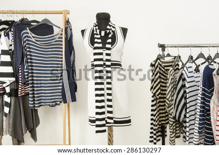 Dressing closet with striped clothes arranged on hangers and a black and white outfit on a mannequin. Colorful wardrobe full of clothes and accessories with stripes pattern. - stock photo