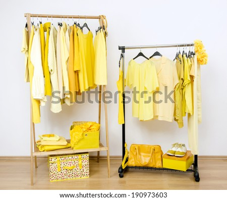 Dressing closet with yellow clothes arranged on hangers. Wardrobe full of all shades of yellow clothes, shoes and accessories. - stock photo