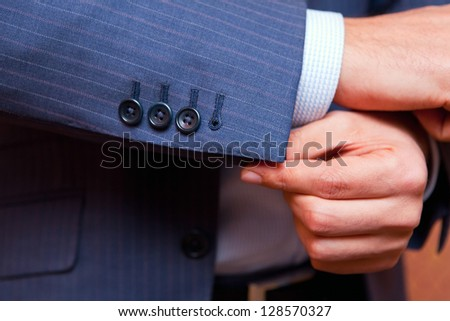 dressing. Closeup of a man in blue striped jacket correcting sleeves. - stock photo