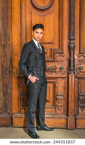 Dressing formally in three pieces black suit, patterned necktie, vest, leather shoes, hands in pockets, a young handsome businessman is standing by an old fashion style office door, looking at you.  - stock photo