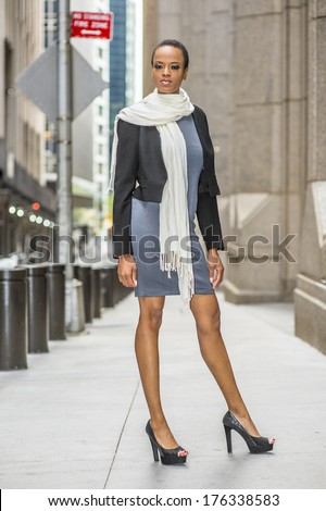 Dressing in a black woolen cropped jacket,  a gray fitted dress, a long white scarf around her neck, open toe high heels,  a young black businesswoman is standing on the street / Street Fashion - stock photo