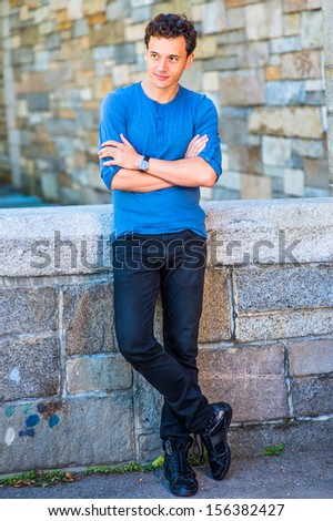 Dressing in a blue long sleeves with roll-tab Henley shirt, black jeans, leather sneakers, wearing a wristwatch, crossing arms,  a young handsome guy is relaxing outside. / Relaxing Outside - stock photo