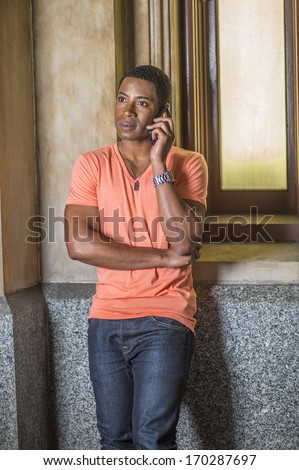 Dressing in a light orange short sleeve V neck shirt, jeans,  a young handsome black student is standing by a small window, listening to the phone. / Making a Phone Call  - stock photo
