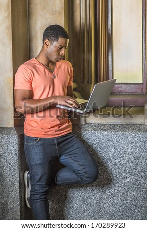 Dressing in a light orange short sleeve V neck shirt, jeans, a young handsome black student is standing by a small window, working on a laptop computer. / Study Outside  - stock photo