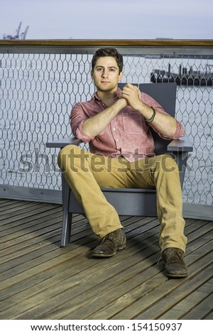 Dressing in a light red shirt, dark yellow pants and brown shoes, a young handsome guy is sitting on a chair in the deck by the river, clutching hands, relaxing. / Sitting down and Relaxing  - stock photo