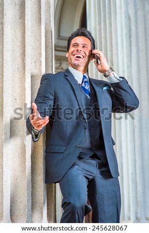 Dressing in dark blue three piece suit, necktie, a handsome, sexy, middle age businessman is standing outside office, looking up, laughing, waving a hand, making a phone call on his mobile phone. - stock photo
