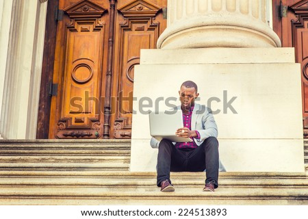 Dressing in light gray blazer, black pants, brown leather shoes, a young black guy is sitting on stairs, outside old fashion style office building, looking down, reading, working on laptop computer.  - stock photo