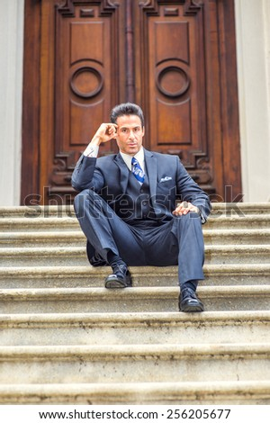 Dressing in suit, necktie, a handsome, sexy, middle age businessman sitting on stairs in front of office, thinking. Concept of businessman thinking, relaxing before busy day of working, meeting.  - stock photo