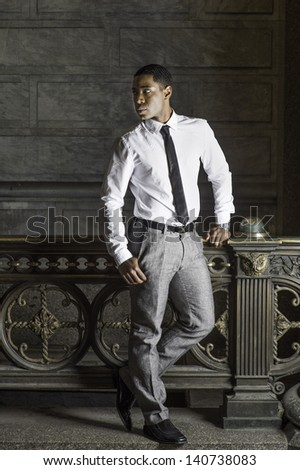 Dressing in white shirt, a black tie, gray pants, a young handsome black businessman is standing by a railing and waiting for you/Waiting for You - stock photo