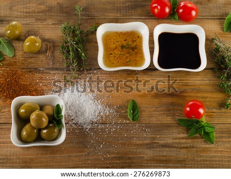 Dressing ingredients on a rustic wooden background. Olive oil, balsamic vinegar, herbs, salt and pepper. Top view - stock photo