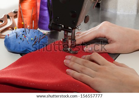 Dressmaker sewing a dress with red material - stock photo