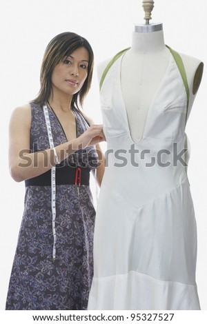 Dressmaker sewing on mannequin - stock photo