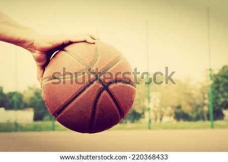 Dribbling the ball on basketball court. Streetball, training, sport. Real and authentic, vintage mood. - stock photo