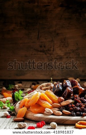Dried apricots, dates, raisins and various nuts, vintage wooden background, selective focus - stock photo