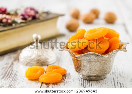 Dried apricots in traditional silver bowl on wooden white table - stock photo