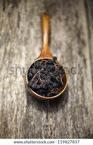 Dried aronia berries in a wooden spoon on a rustic wooden board - stock photo
