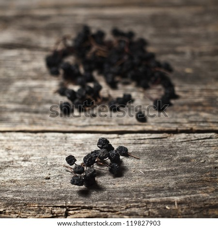 Dried aronia berries on a rustic wooden board - stock photo
