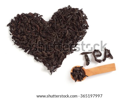 Dried black tea in shape of heart on white background. Word tea - stock photo