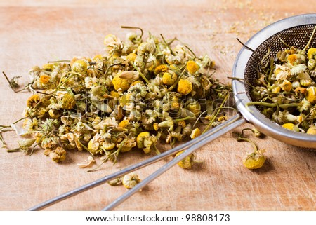dried chamomile flowers with colander on wooden plate - stock photo