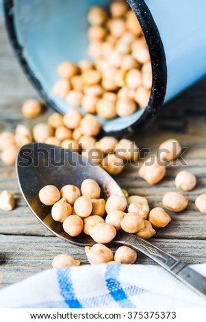 dried chickpeas in a spoon and a blue cup on a gray wooden board,close-up - stock photo