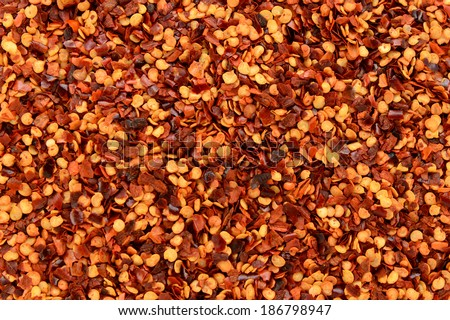 Dried chili flakes and seeds, or crushed red pepper, abstract background texture - stock photo