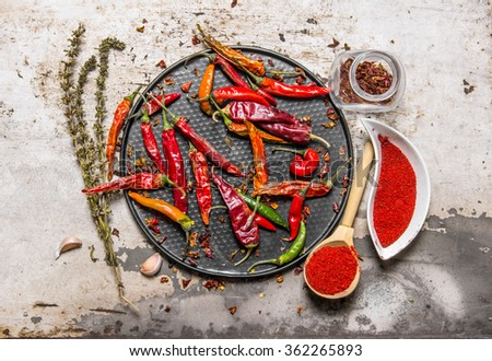 Dried chili peppers on a tray with crushed red pepper in the cups, with herbs. On rustic background. Top view - stock photo