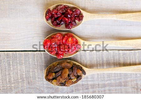 Dried cranberry, cherry, raisin on wooden background - stock photo