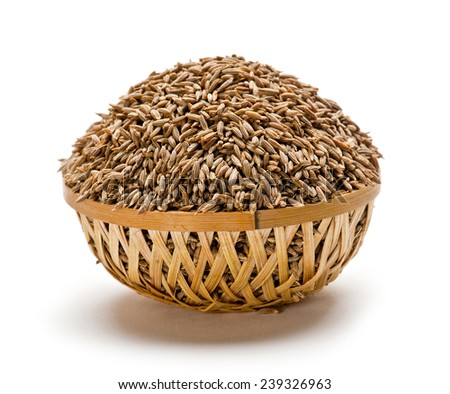 Dried cumin seeds pile in wooden basket isolated on white background - stock photo