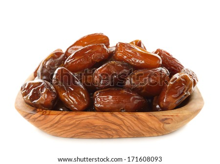 dried dates in a wooden bowl isolated on white background - stock photo