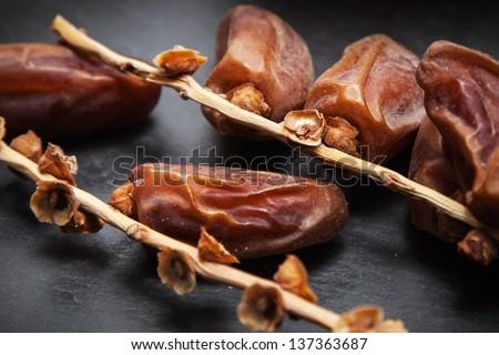 dried dates on vine resting on a dark gray slate board - stock photo