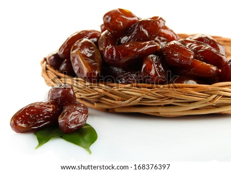 Dried dates on wicker plate isolated on white - stock photo